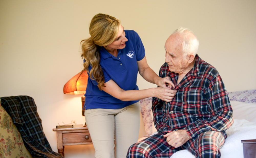 Senior Homecare by Angels's caregiver helping to dress our client, Live-in.